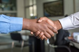 Two people shaking hands after talking about ways to reduce moving stress when moving with kids