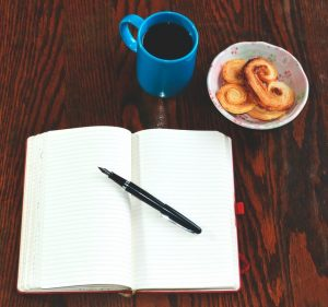 A notebook, a pen, a cup of coffee, and some snacks on a desk