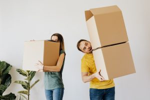 two people carrying boxes.