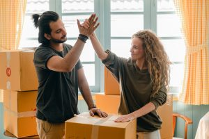 Couple giving high five while standing near a pile of boxes after moving